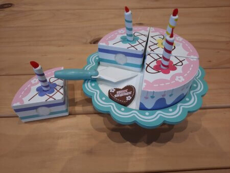 Wooden birthday cake on stand cut